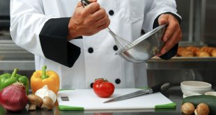 Caucasian chef mixing something in a bowl with fresh vegetables on a cutting board in front of him in a restaurant kitchen.